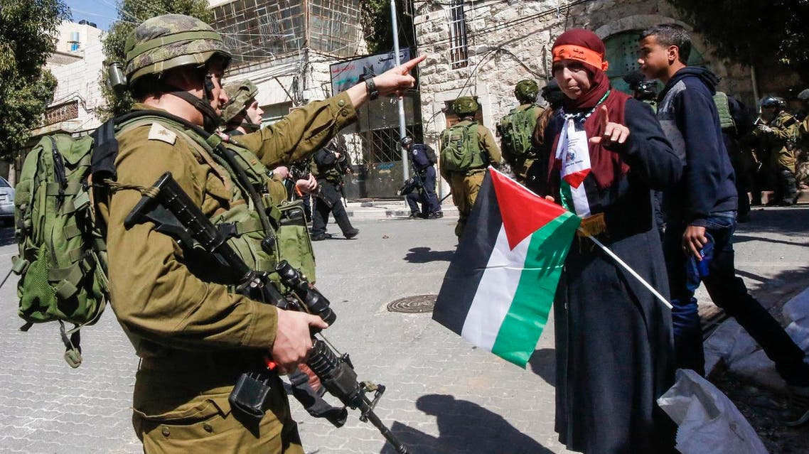 An Israeli soldier points at a woman carrying a Palestinian flag during a protest calling for the opening of Shuhada Street, which is largely closed off to Palestinians, near a Jewish settler enclave in the heart of the West Bank city of Hebron, coinciding with the anniversary of a 1994 massacre carried out by a far-right Jewish settler, on February 24, 2017. AFP