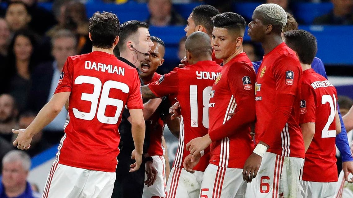 United players argue with referee Michael Oliver, 2nd left, during the English FA Cup quarterfinal soccer match between Chelsea and Manchester United at Stamford Bridge stadium in London, Monday, March 13, 2017. (AP)