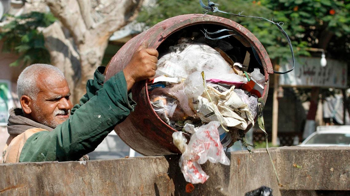 In this Thursday, Aug. 16, 2012 photo, a waste collector unloads garbage at a container in Cairo. (AP)