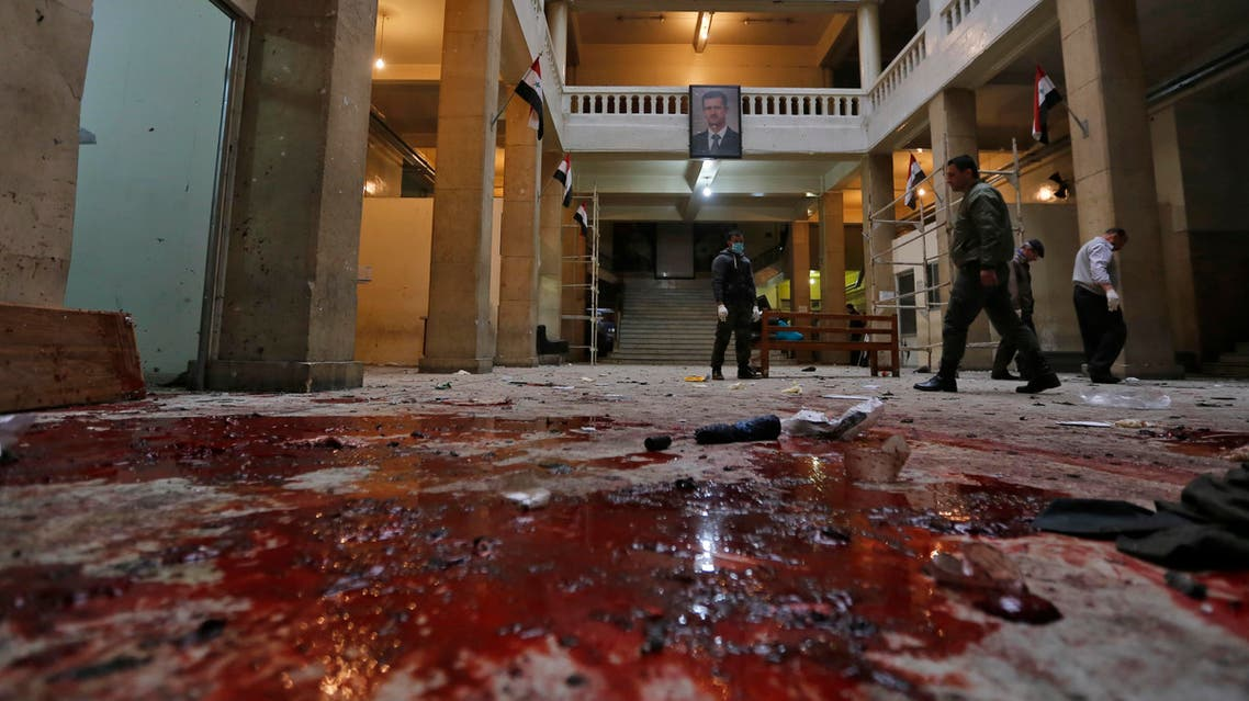Syrian security forces inspect the scene of a reported suicide bombing at the old palace of justice building in Damascus on March 15, 2017.