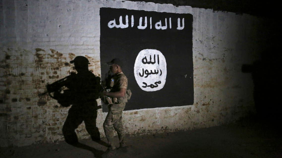 In this March 1, 2017 file photo, an Iraqi soldier inspects a recently-discovered train tunnel, adorned with an Islamic State group flag, that belonged to the former Baghdad to Mosul line, that was turned it to a training camp for IS fighters, in western Mosul, Iraq. (AP)