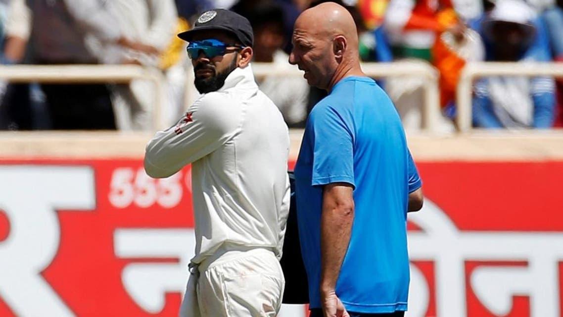 India's captain Virat Kohli (left) walks off the field after injuring himself. (Reuters)
