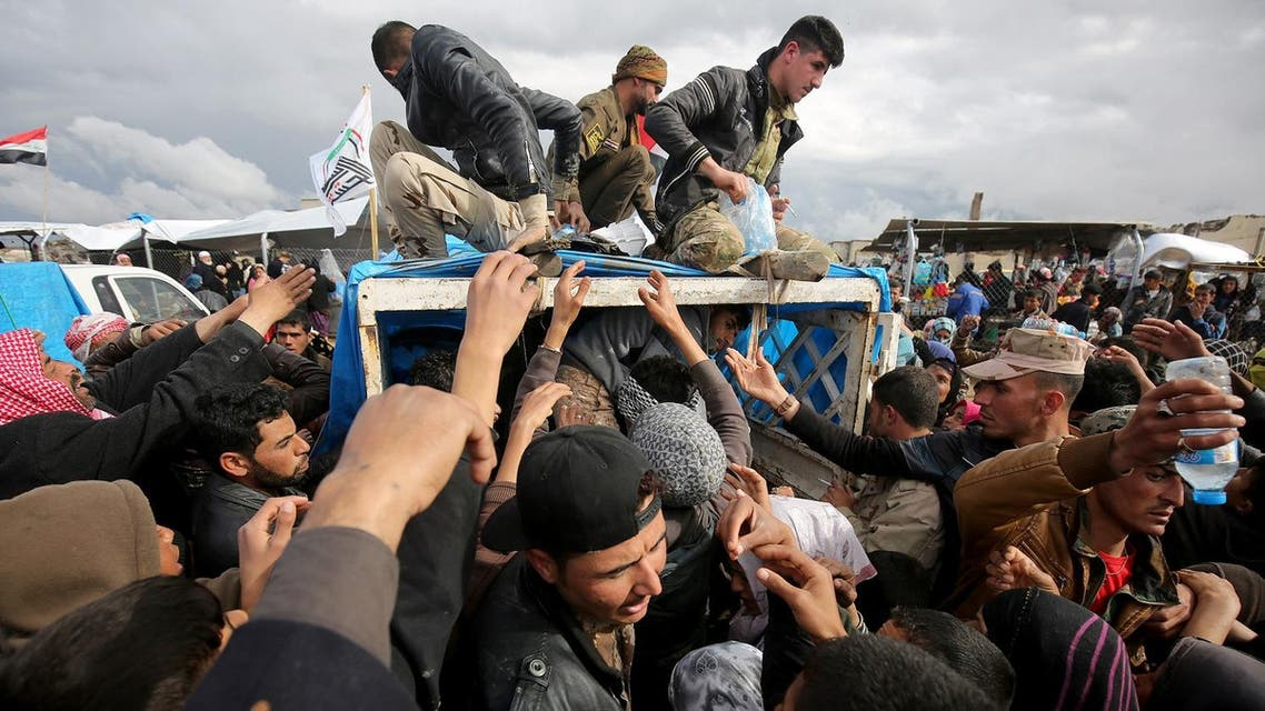 Iraqis, displaced from Mosul, receive aid rations at the Hammam al-Alil camp for the internally displaced, south of Mosul, on March 16, 2017. (AFP)