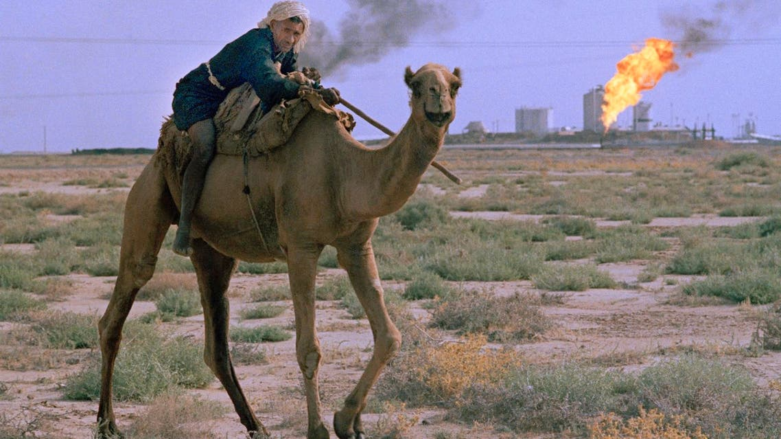 A man rides a camel while unwanted gas byproducts are burned off at a petrochemical factory in the background in the desert near Ahwaz, Iran, July 1971. (AP)