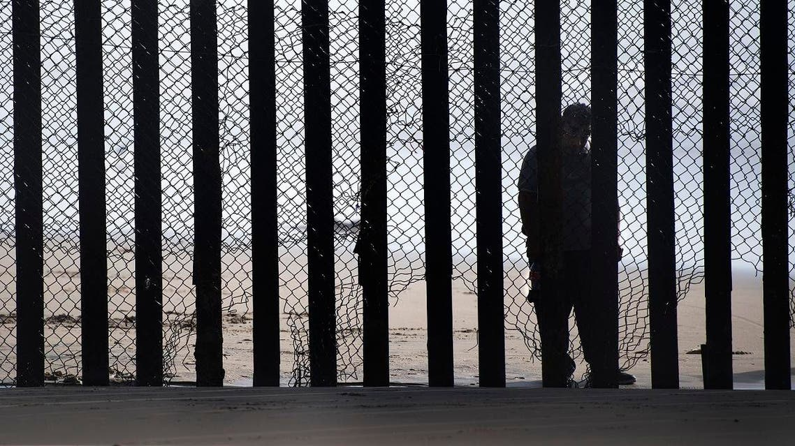 A man stands on the Mexico side of a border fence separating the beaches at Border Field State Park, in San Diego, CA. (AFP)