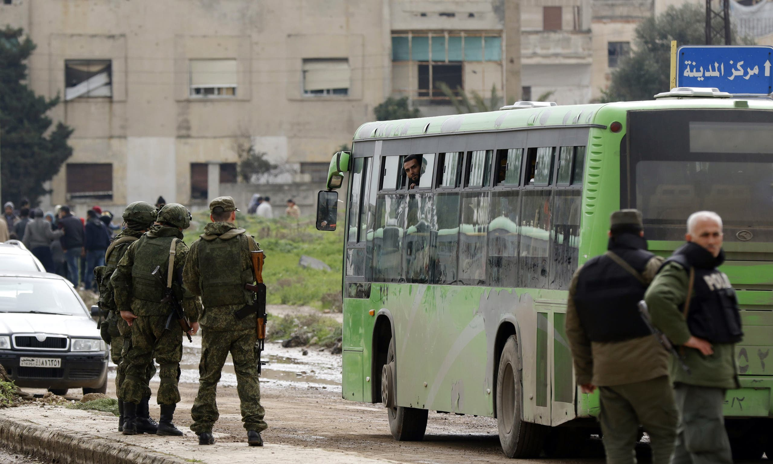 Members of the Russian Military police stand guard as a bus drives past during the first phase of the Russian-supervised deal to complete the evacuation of fighters and civilians, on the edge of the rebel-held Waer neighbourhood in the central city of Homs on March 18, 2017.