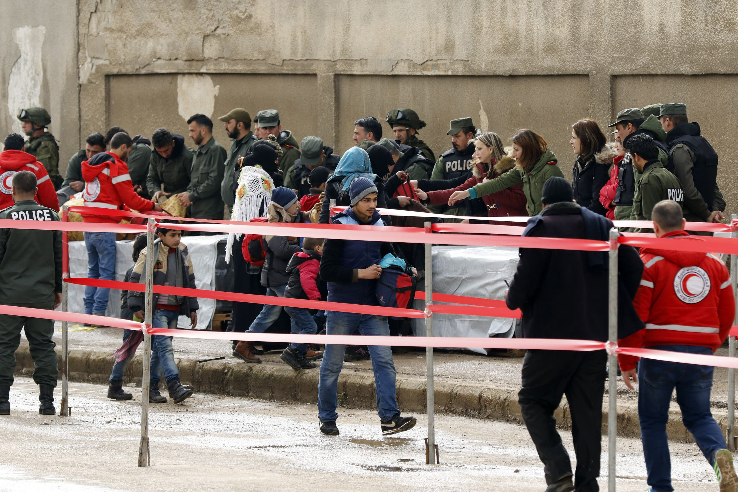 Syrian opposition fighters and their families are searched as they arrive at a checkpoint, manned by regime forces and Red Crescent members, on the edge of the rebel-held Waer neighbourhood in the central city of Homs on March 18, 2017, during the first phase of the Russian-supervised deal to complete the evacuation of fighters and civilians.
