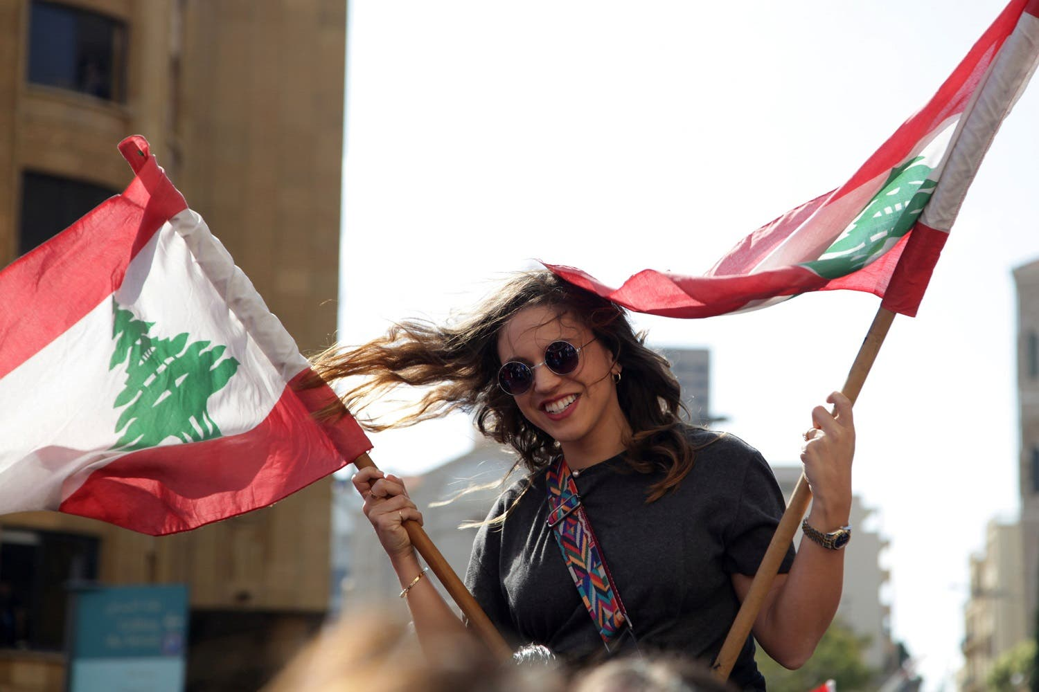A protester waves Lebanese national flaga during a demonstration against a proposed tax increase in front of the government palace in Beirut. (Reuters)