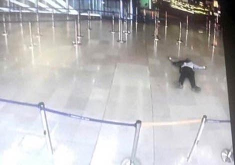 A picture taken from the screen of a monitor on March 18, 2017 shows a man lying on the ground of a terminal building at Paris' Orly airport after he was shot by French security forces for taking a weapon from a soldier. (AFP)