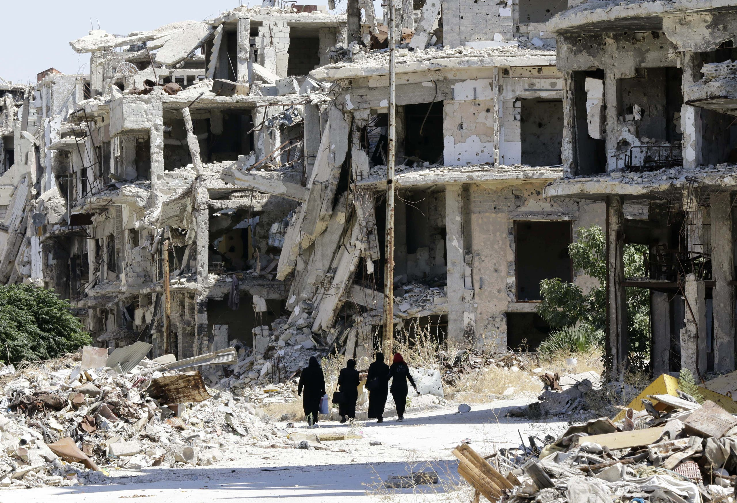 (FILES) This file photo taken on September 19, 2016 shows Syrian women walking in between destroyed buildings in the government-held Jouret al-Shiah neighbourhood of the central Syrian city of Homs. Syria's war has killed just over 320,000 people since it erupted six years ago, the Britain-based Syrian Observatory for Human Rights said on March 13, 2017, noting that a fragile ceasefire had helped to slow the rising death toll. AFP