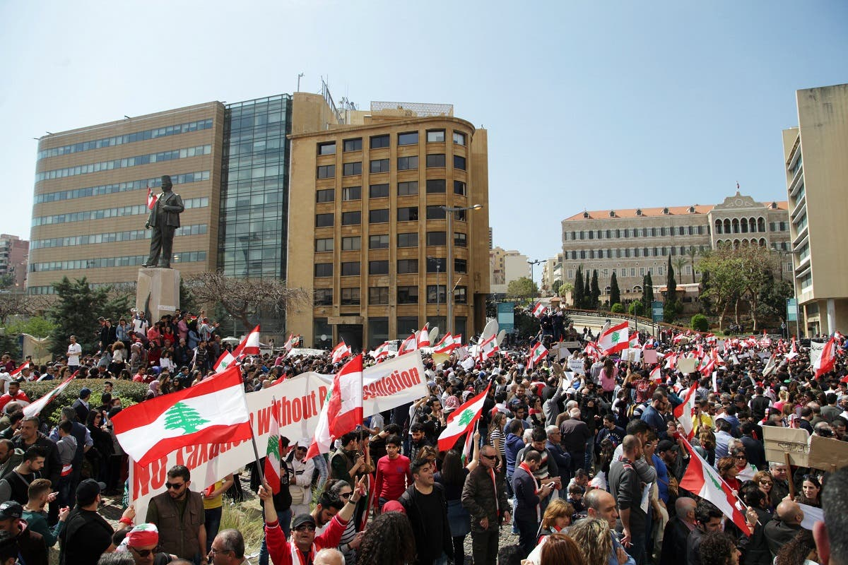 Protesters wave Lebanese national flags during a demonstration against proposed tax increase, in front of the government palace in Beirut. (Reuters)