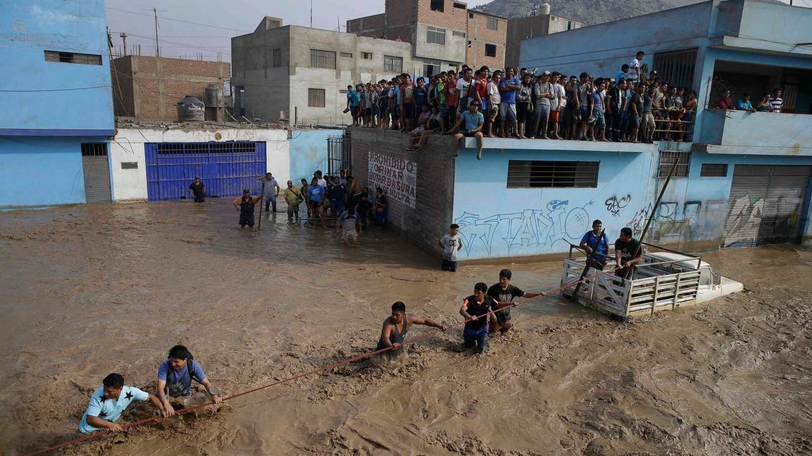 A group of people, stranded in flood waters, hold onto a rope as they walk to safety in Lima, Peru, Friday, March 17, 2017. (AP)