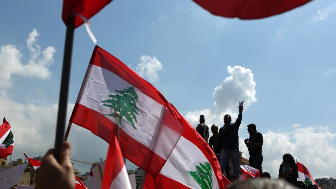 Lebanese wave their national flag during a protest in downtown Beirut. (AFP)