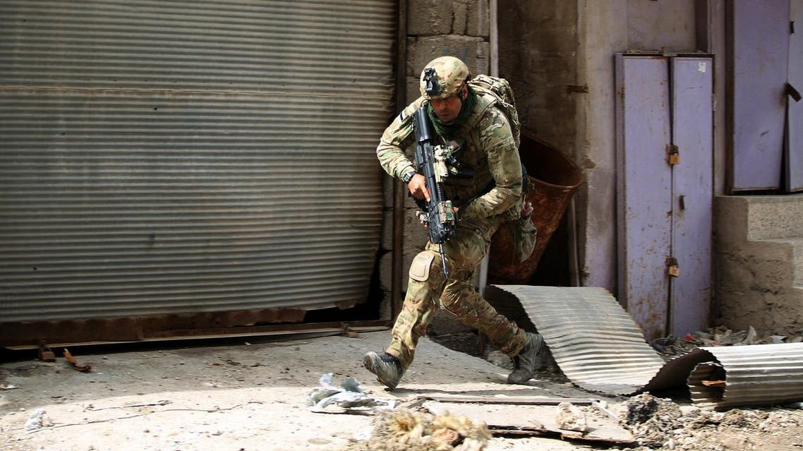 A member of the Iraqi forces, consisting of the Iraqi federal police and the elite Rapid Response Division, runs for cover as they advance in the Old City in western Mosul on March 19, 2017, during the offensive to retake the city from Islamic State (IS) group fighters. (AFP)