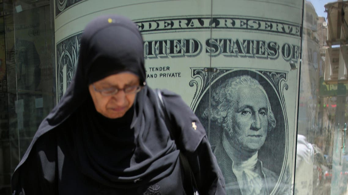 A woman walks past a currency exchange bureau advertisement showing images of the U.S dollar and other currencies in Cairo, Egypt August 3, 2016. Picture taken August 3, 2016. REUTERS/Mohamed Abd El Ghany