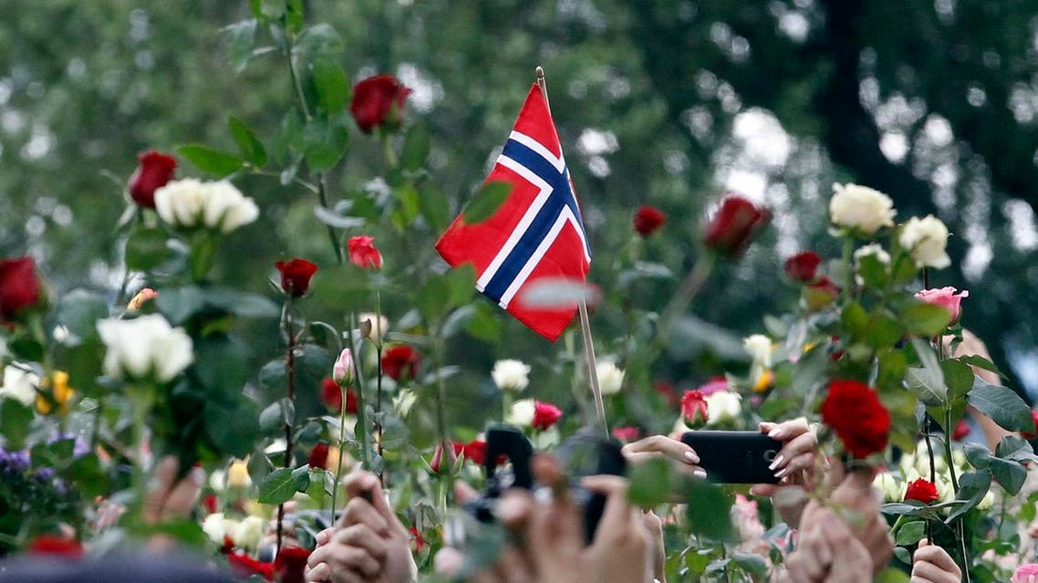 People holding roses take part in a march to mourn for the victims of the killing spree and bomb attack in downtown Oslo July 25, 2011. At least 100,000 people, many carrying white or red roses, rallied in Oslo on Monday to show support for victims of attacks that killed 76 people, police said. REUTERS/Fabrizio Bensch (NORWAY - Tags: CIVIL UNREST CRIME LAW)