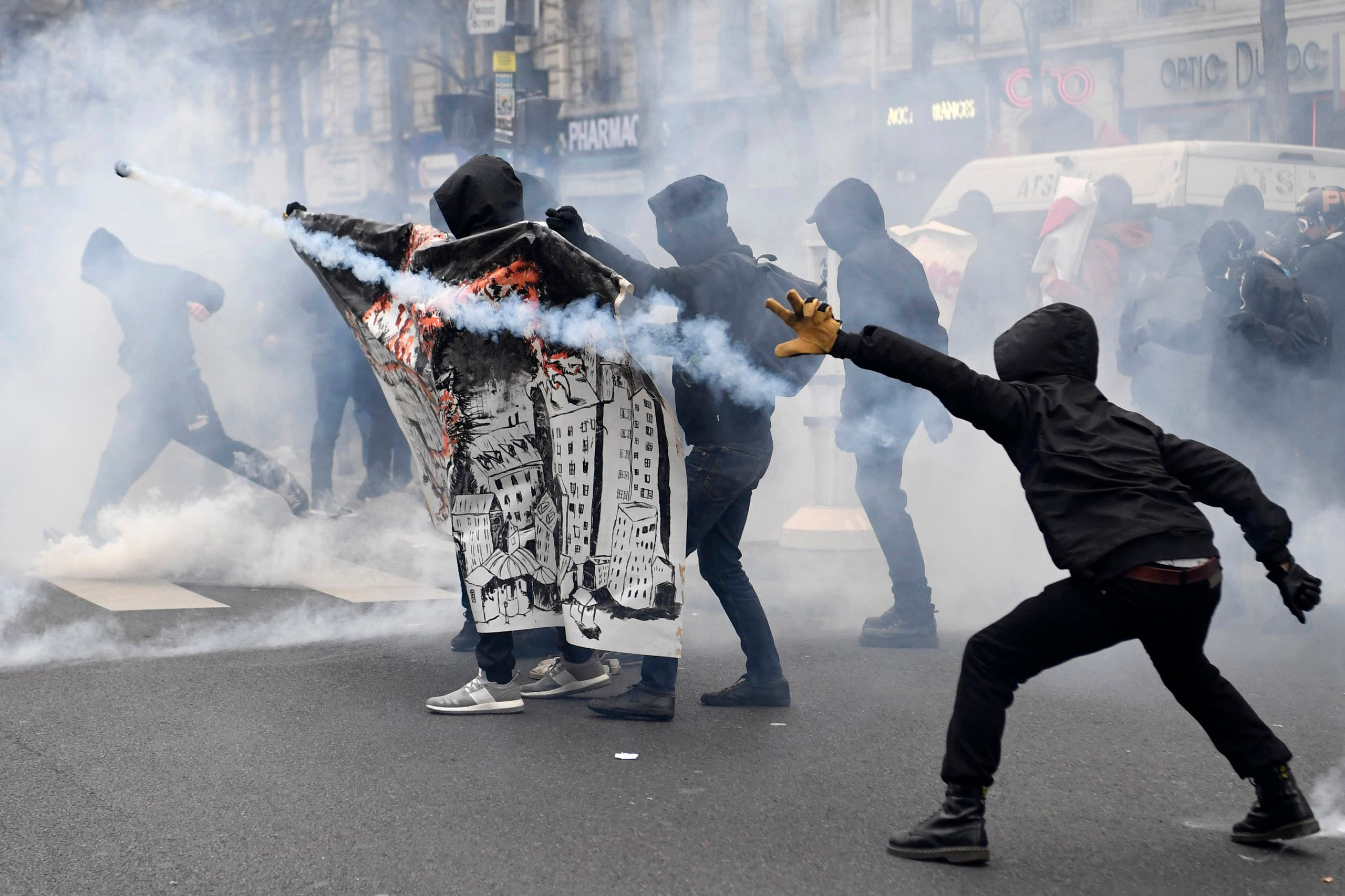 Hooded participants throw back tear gas canisters as they clash with police within a demonstration called by the families of the victims of alleged police brutality, AFP