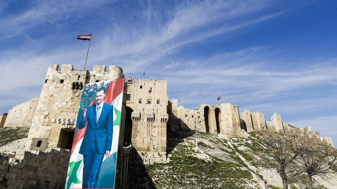 A picture taken on March 9, 2017 in Aleppo shows giant banners of Bashar al-Assad outside the historic citadel on the outskirts of the old city. (AFP)