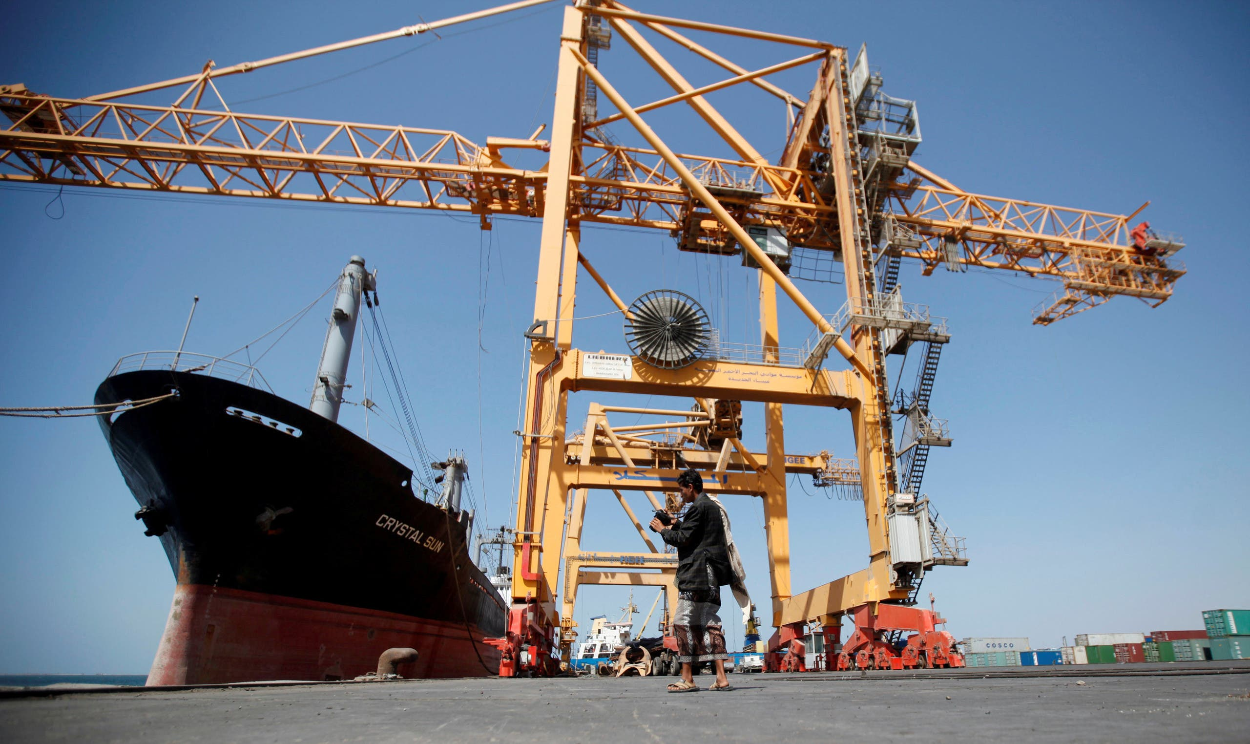 A Houthi militia media officer checks a camera next to giant cranes, damaged by Saudi-led air strikes, at a container terminal at the Red Sea port of Hodeidah, Yemen November 16, 2016