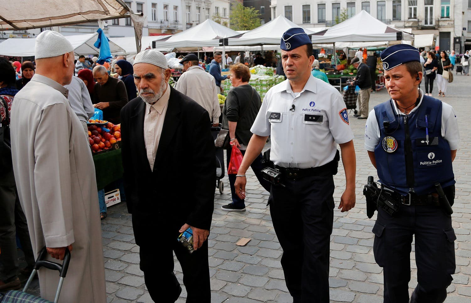Despite the pride that Chatt says the Molenbeek community feels towards him, there is still stigma attached to working for the police. Officers Ann Vercammen (R) and Tarek Chatt patrol at a market in Belgium. (File Photo: Reuters)