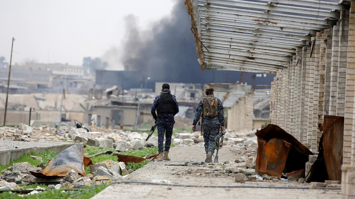 Federal police members carry their weapons as they walk through a destroyed train station during a battle against Islamic State militants, in Mosul. REUTERS