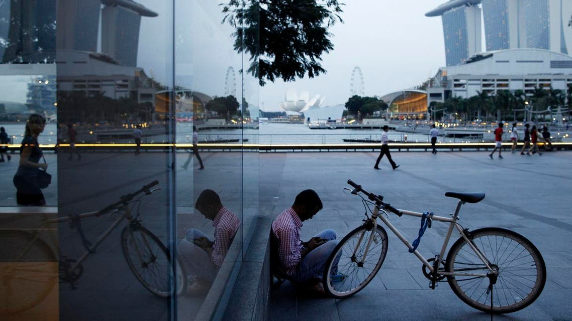 A migrant worker checks his mobile phone at the Marina Bay Promenade in the central business district of Singapore. (File Photo: Reuters)