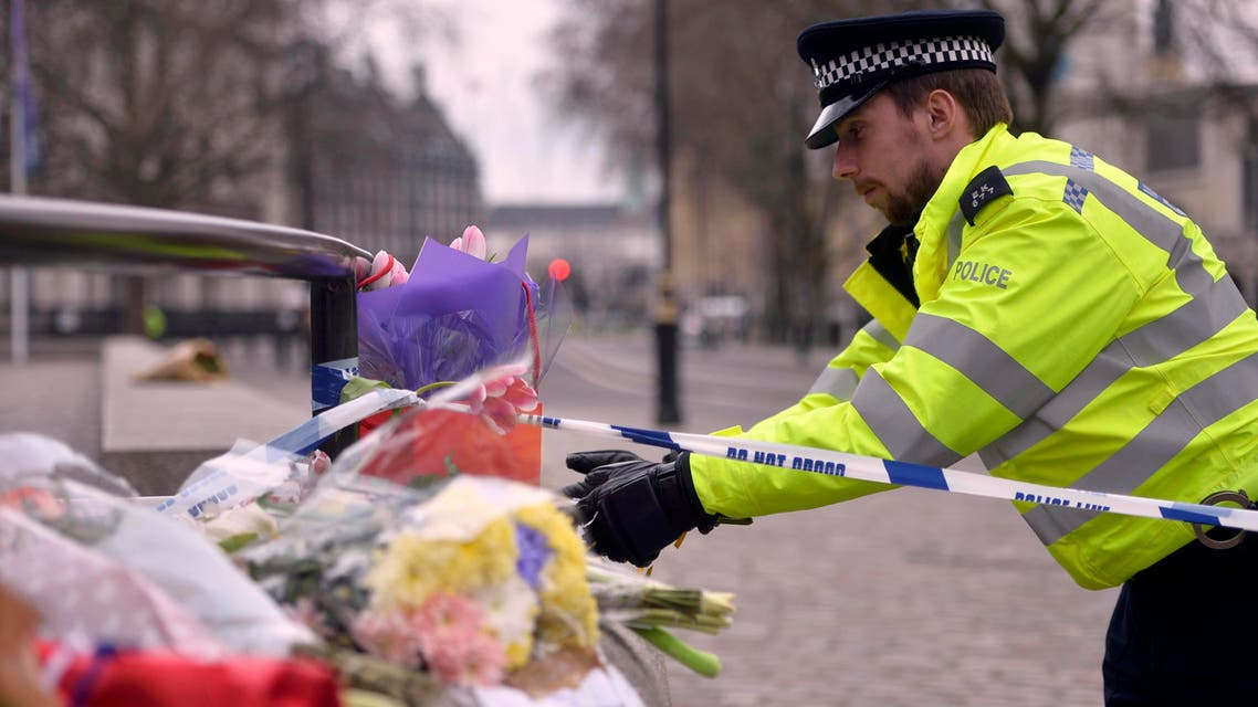 A police officer reaches out to floral tributes in Westminster the day after an attack, in London, Britain March 23, 2017. (Reuters)