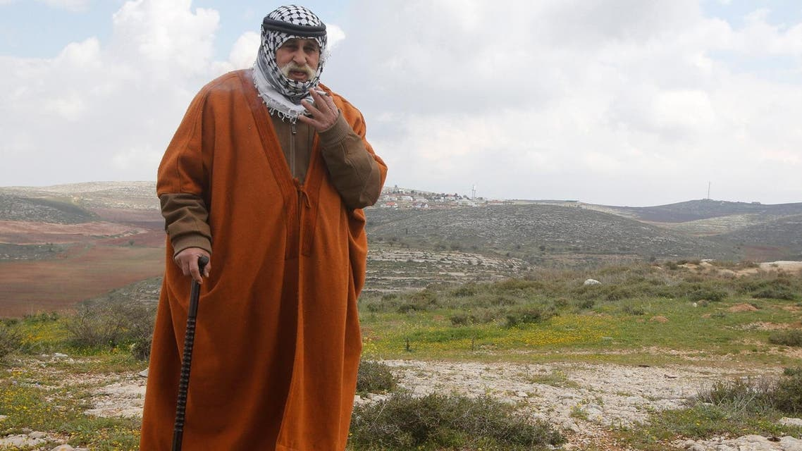 A Palestinian man smokes a cigarette as he walks during a tour by Palestinian chief negotiator Saeb Erekat and foreign diplomats near Jewish settlements in the West Bank village of Jaloud near Nablus March 16, 2017. (Reuters)