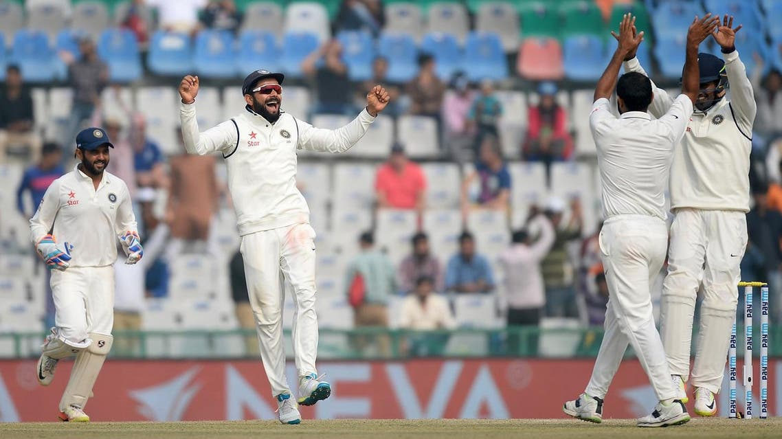 India captain Virat Kohli (2L), bowler Mohd Shami (R) and teammates celebrate the wicket of England batsman Adil Rashid on the fourth day of the third Test match between India and England at The Punjab Cricket Association Stadium in Mohali on November 29, 2016. (AFP)