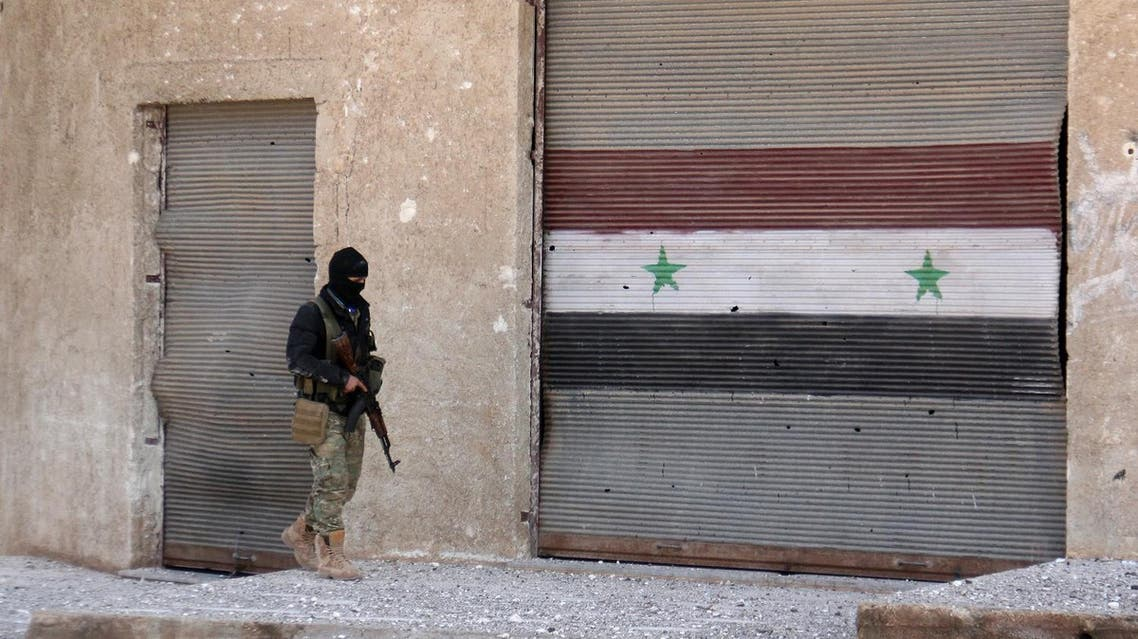 A rebel fighter walks past a roller shutter bearing the Syrian flag, in the village of Rahbet Khattab in the Hama province on March 23, 2017. Jihadists and allied rebels claimed more ground against Syrian government forces in central Hama province, the Syrian Observatory for Human Rights monitor said. AFP