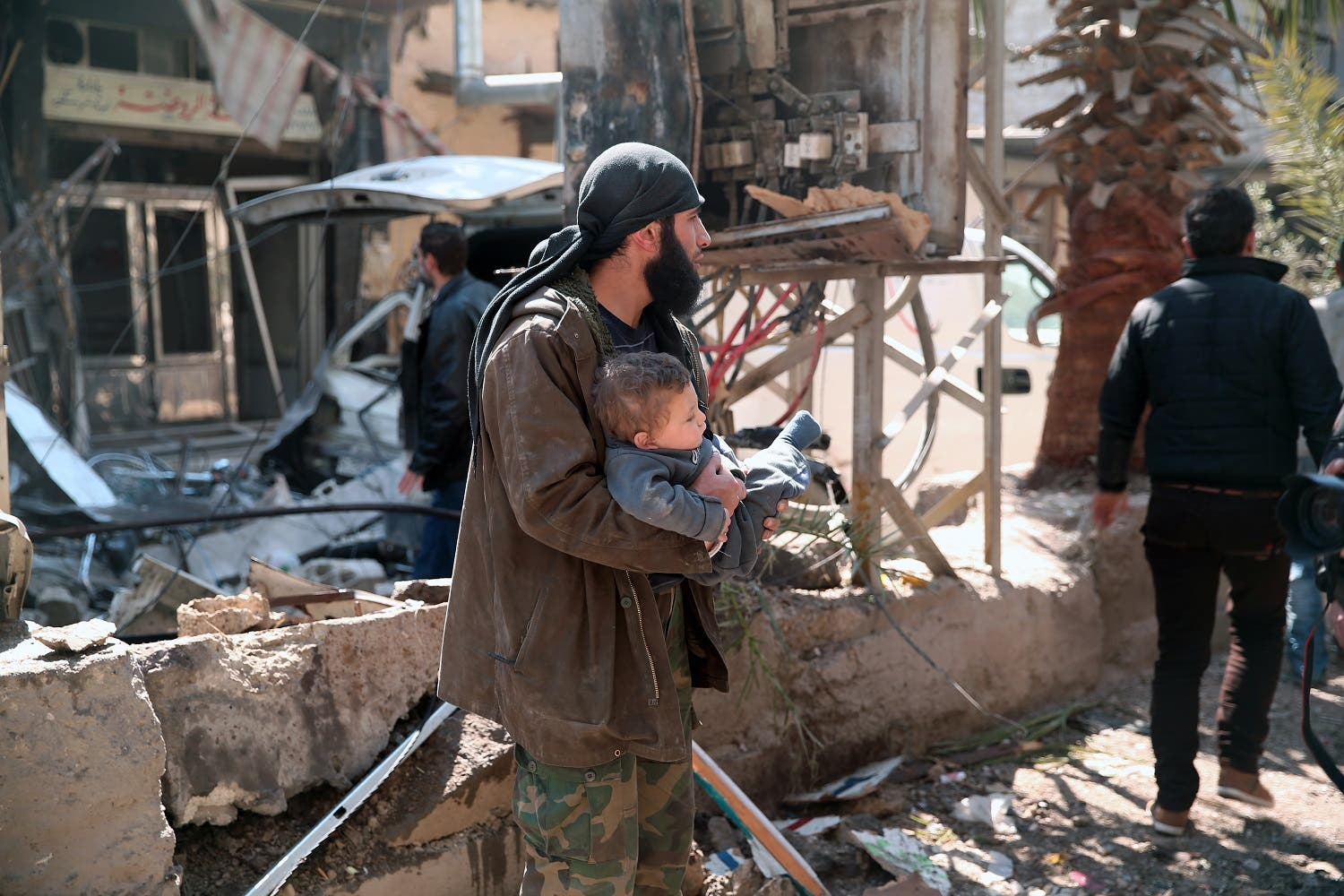 A Syrian man carries a child following reported air-strikes on the rebel-held town of Hamouria, in Eastern Ghouta outside Syria's capital Damascus, on March 25, 2017.AFP