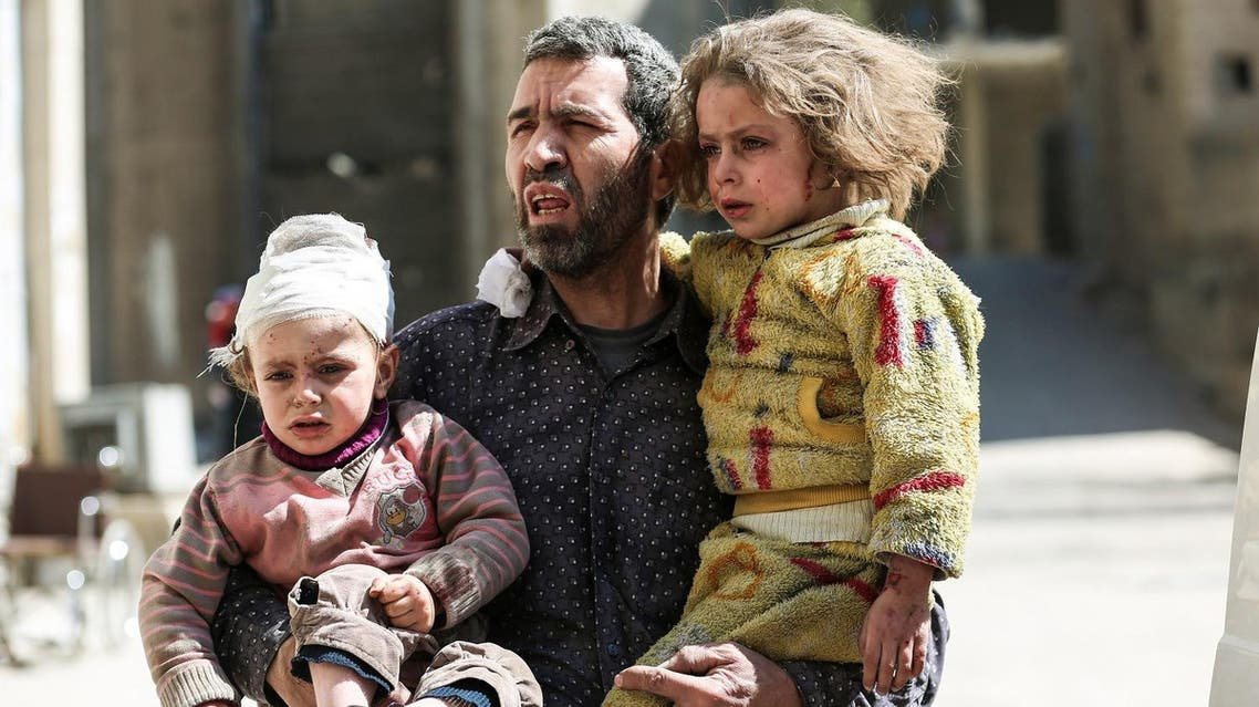 A Syrian man carries two injured children after a reported air strike in the rebel-controlled town of Hamouria, in the eastern Ghouta region on the outskirts of the capital Damascus, on March 25, 2017.  AFP