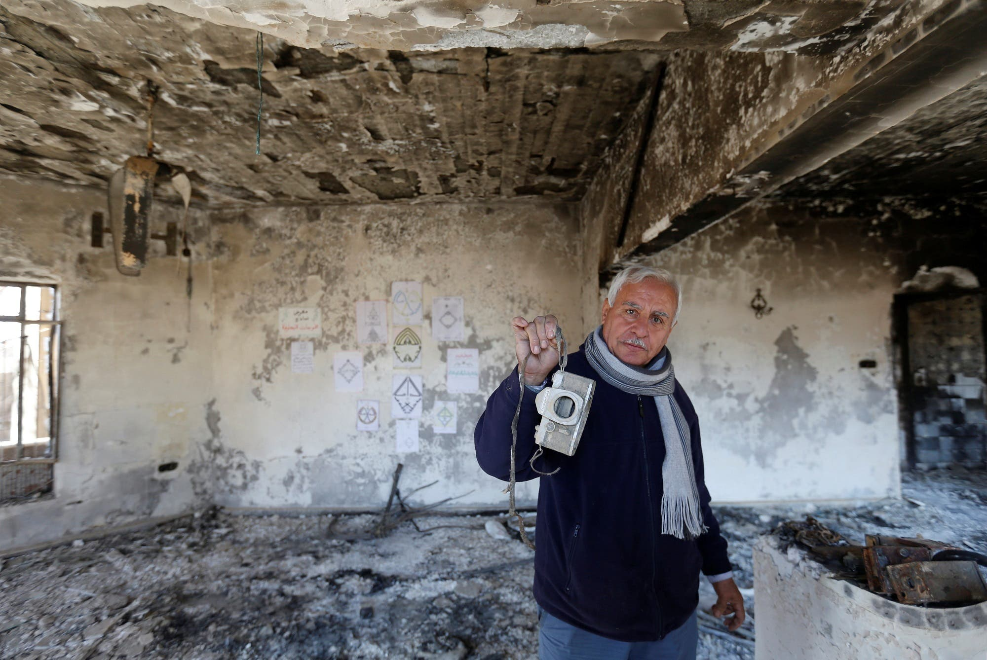 An Iraqi Christian man shows his old camera at his house, which was burned by Islamic State militants before they fled the area, in Qaraqosh, Iraq, February 7, 2017. REUTERS/Muhammad Hamed