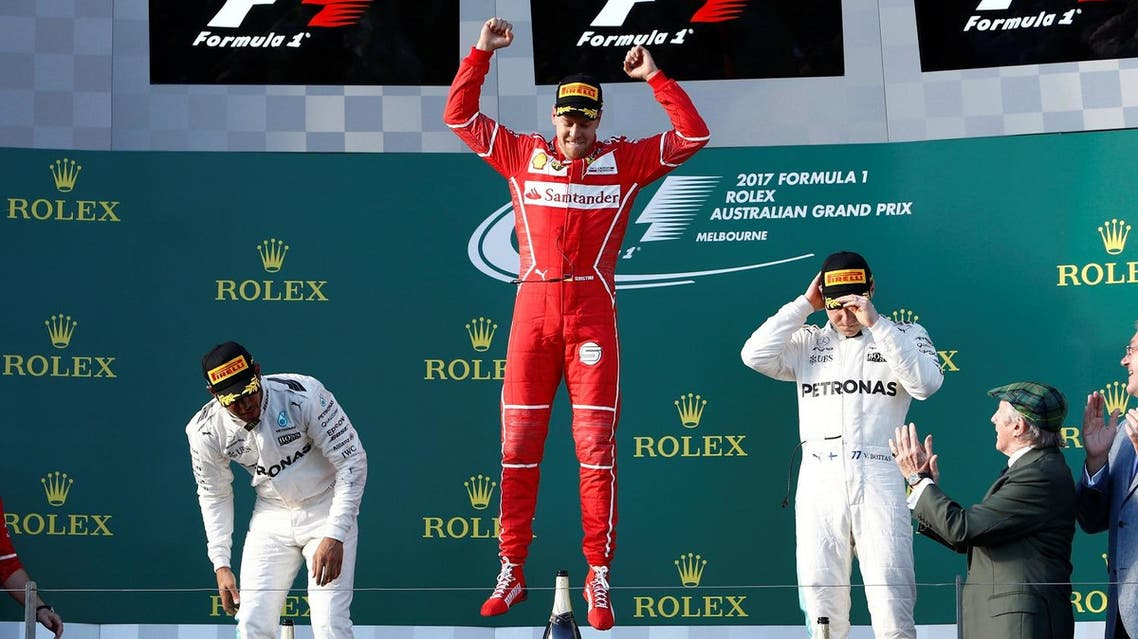 Ferrari driver Sebastian Vettel of Germany (center) leaps in celebration alongside Mercedes driver Lewis Hamilton of Britain (left) and team mate Valtteri Bottas of Finland. (Reuters)