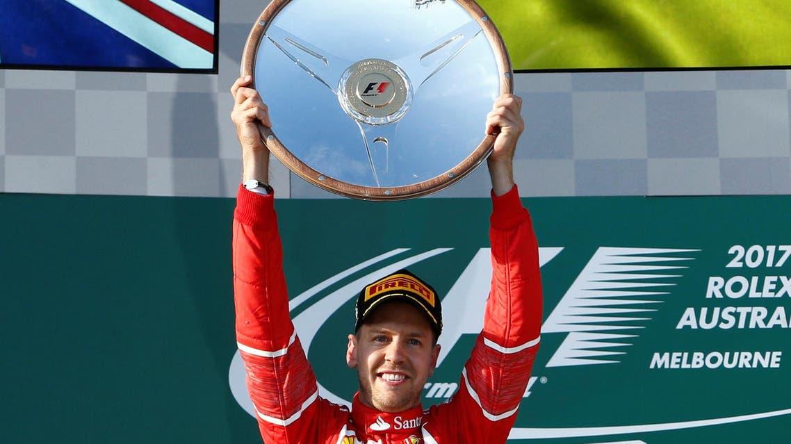 Formula One - F1 - Australian Grand Prix - Melbourne, Australia - 26/03/2017 - Ferrari driver Sebastian Vettel of Germany holds aloft the trophy as he celebrates winning the Australian Grand Prix. REUTERS/Brandon Malone