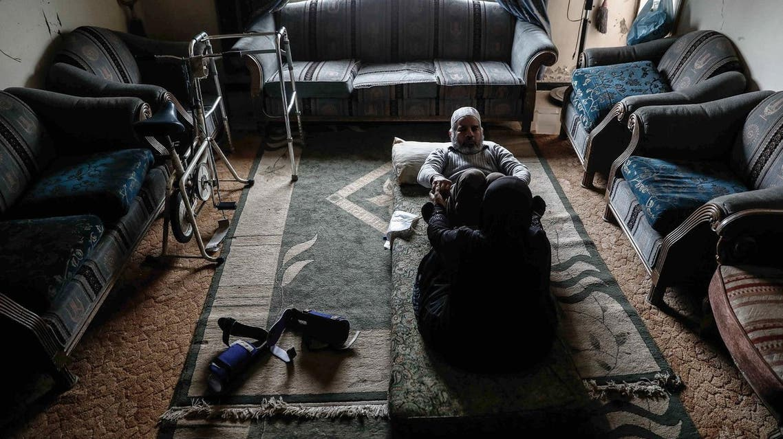 Syrian woman assists husband with rehab exercises amid war in rebel-held Douma