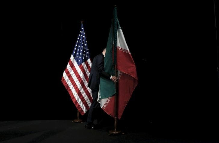 A staff member removes the Iranian flag from the stage during the Iran nuclear talks in Vienna, Austria July 14, 2015. (Reuters)