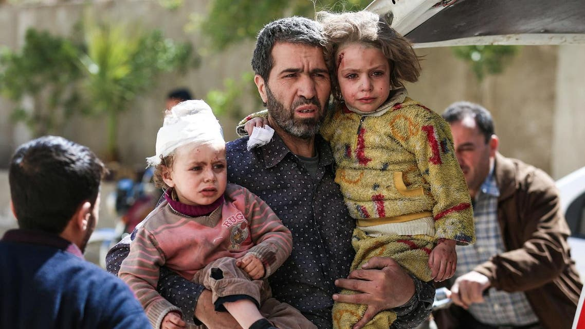 A Syrian man carries two injured children after a reported air strike in the rebel-controlled town of Hamouria, in the eastern Ghouta region on the outskirts of the capital Damascus, on March 25, 2017. (AFP)