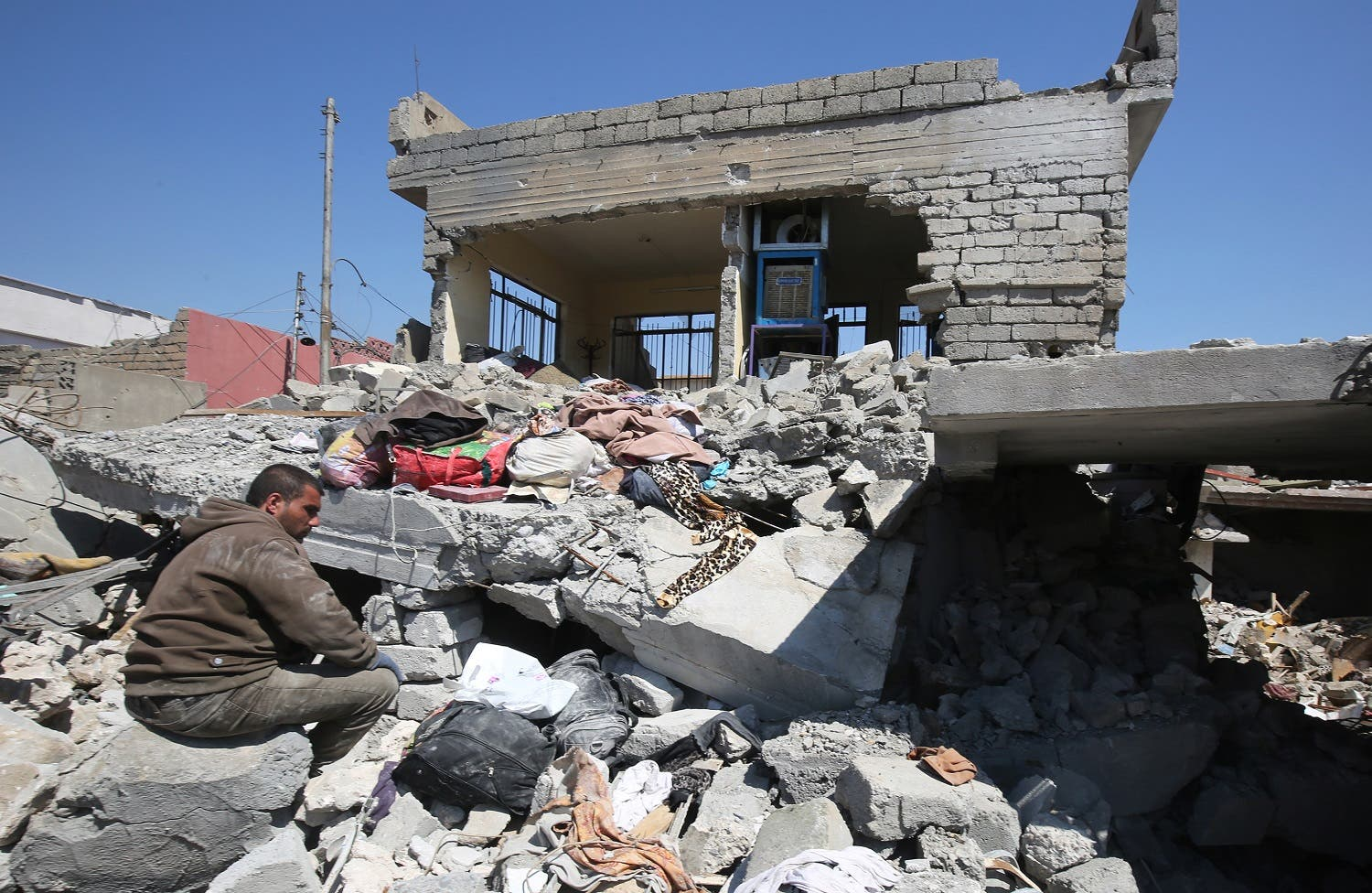 An Iraqi man sits amid the rubble of destroyed houses in the Mosul al-Jadida area on March 26, 2017. (AFP)
