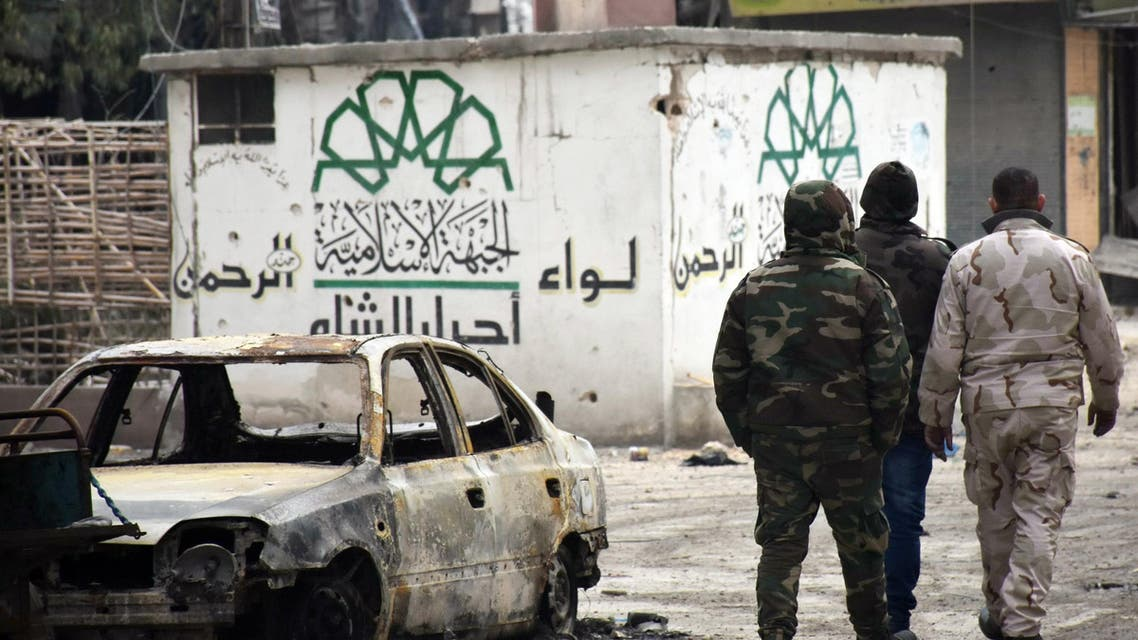 Syrian government forces walk past a destroyed vehicle and a graffiti bearing the emblem of the Ahrar Al-Sham's Rahman Brigade of the Islamic Front (L) in the former rebel-held Sukkari district in the northern city of Aleppo on December 23, 2016 after Syrian government forces retook control of the whole embattled city. Syrian troops cemented their hold on Aleppo after retaking full control of the city, as residents anxious to return to their homes moved through its ruined streets. (AFP)