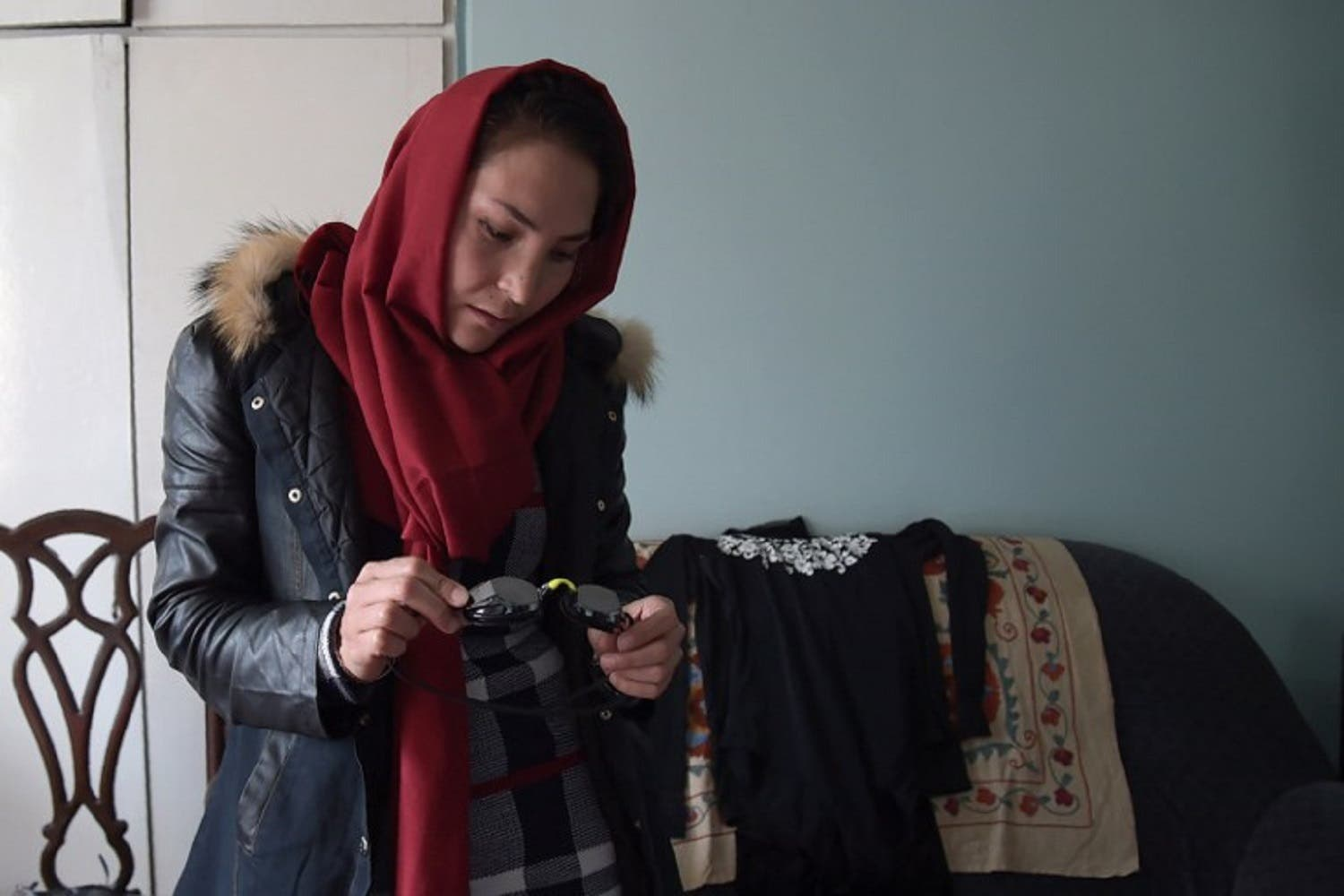 Afghan swimmer and Coach Elena Saboori, 25, holds her goggles during an interview with AFP in a house in Kabul. (AFP)