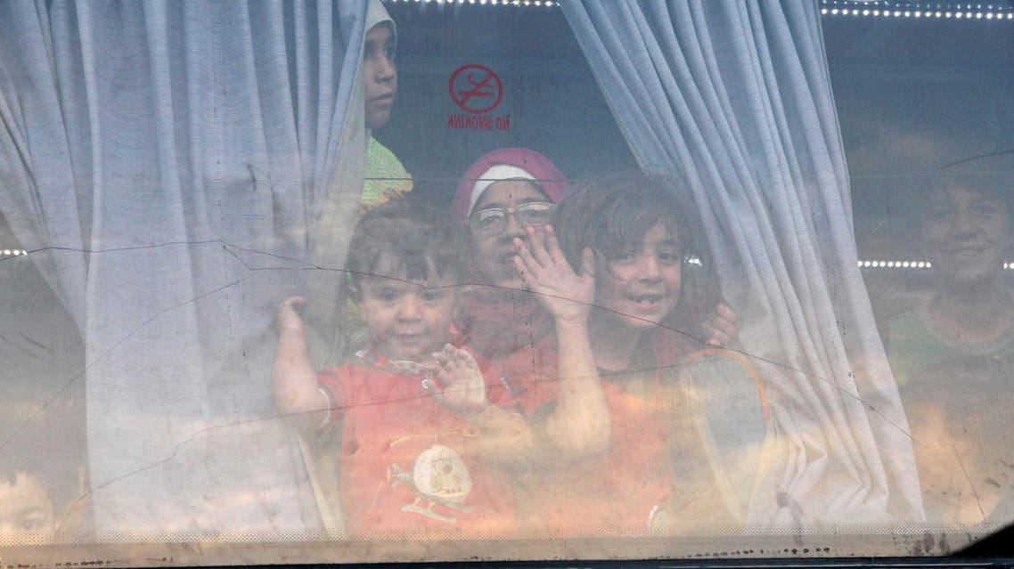 Children evacuees, from the besieged rebel-held Syrian town of Zabadani gesture from inside a bus upon their arrival at an exchange point supervised by the Syrian Arab Red Crescent, in the town of Qalaat al-Madiq, in Hama province, Syria April 21, 2016. (Reuters)