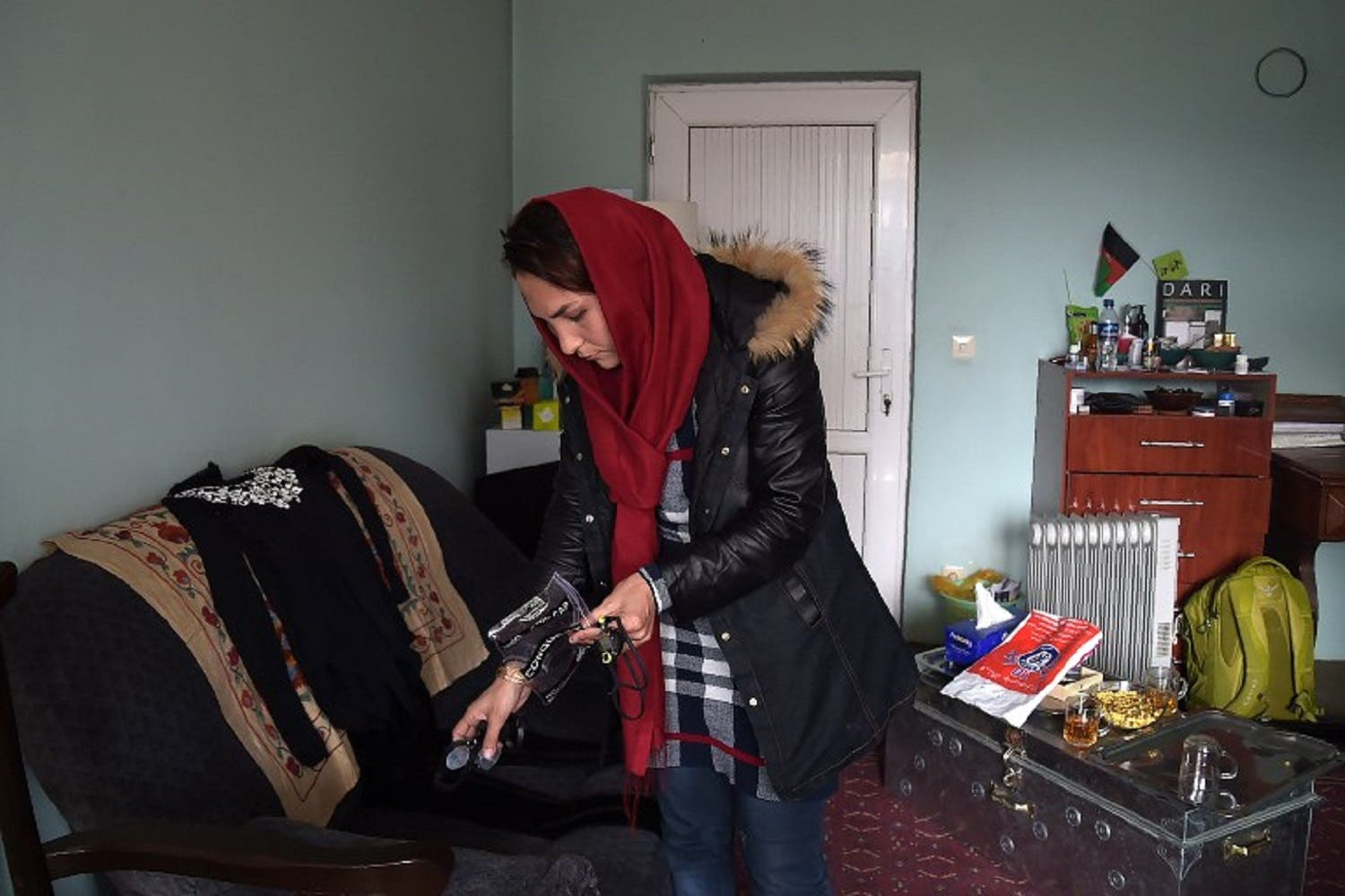 Elena Saboori, 25, head of the newly created Women's Swimming Committee, gathers her gear during an interview in a house in Kabul. (AFP)