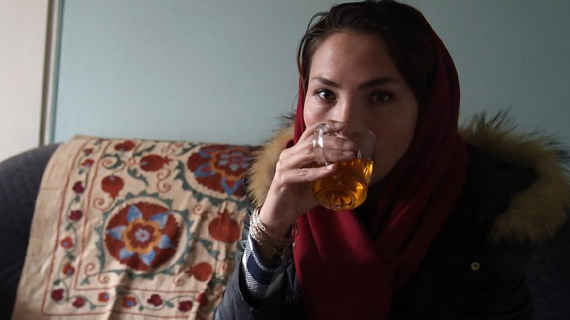 Afghan swimmer and Coach Elena Saboori, 25, head of the newly created Women's Swimming Committee, drinks tea during an interview in a house in Kabul. (AFP)