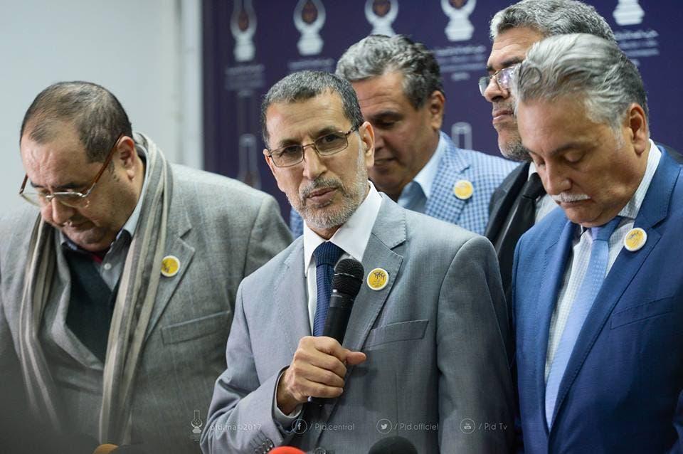 من إعلان التحالف الحكومي ويظهر إدريس لشكر مطأطأ الرأس على يمين سعد الدين العثماني
