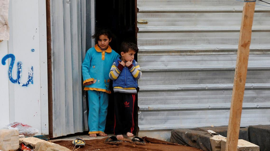 Syrian refugee children stand in front of their family residence during rainy weather at the Al Zaatari refugee camp in the Jordanian city of Mafraq, near the border with Syria December 18, 2016. REUTERS/Muhammad Hamed