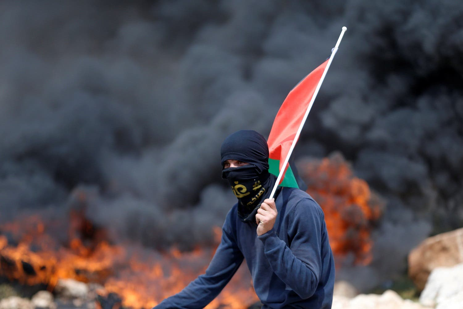 A protester holds a Palestinian flag as smoke rises from burning tyres during clashes with Israeli troops at a protest against Jewish settlements, in al-Mughayyir village near the West Bank city of Ramallah March 24, 2017. (Reuters)