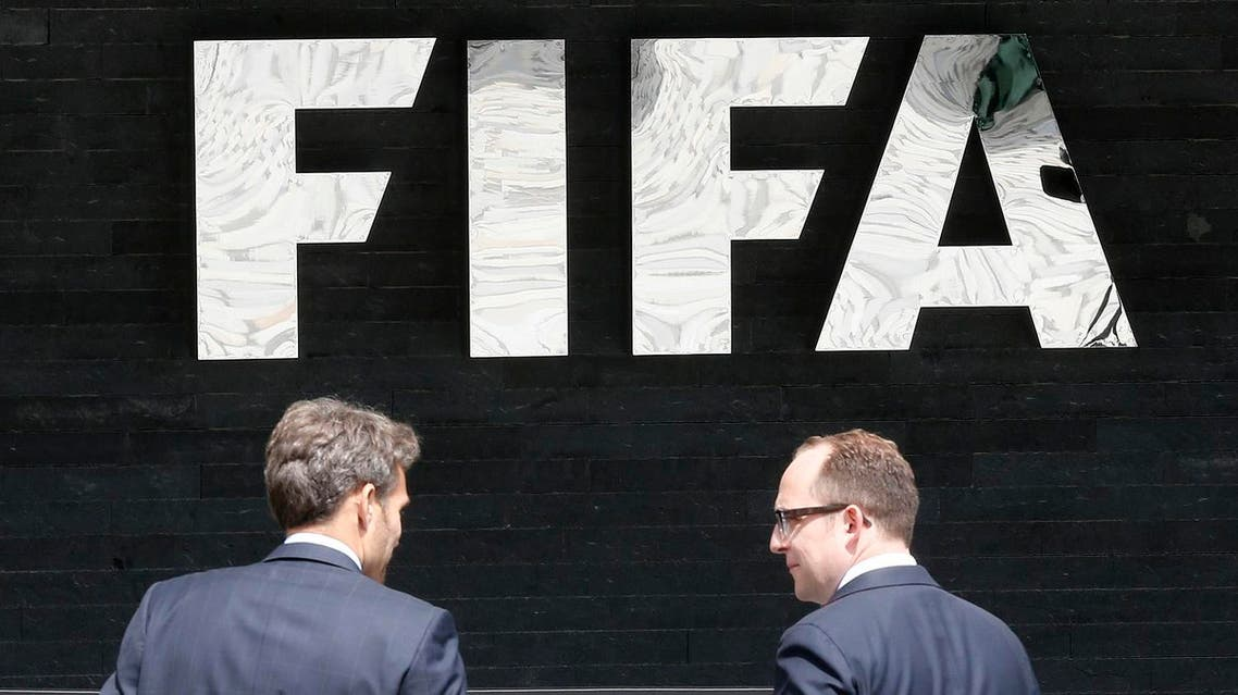 Two men talk to each other in front of the FIFA logo at the FIFA headquarters in Zurich, Switzerland, Wednesday, May 27, 2015. (AP)