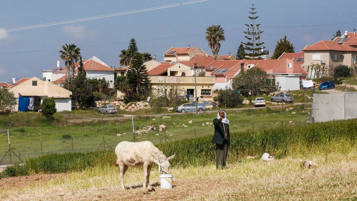 A Palestinian stands next to a donkey as it feeds in the West Bank town of Ramadin, southwest of Hebron, with the Israeli settlement of Eshkolot appearing in the background, on March 25, 2017. (AFP)