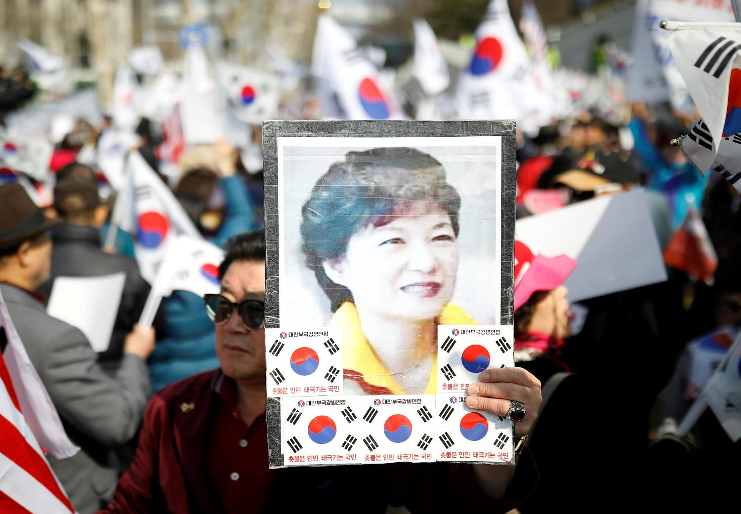 A supporter of Park Geun-hye holds up her portrait during a rally in front of a prosecutor's office in Seoul on March 21, 2017. (Reuters)